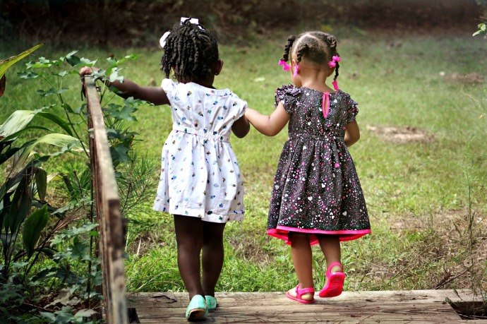 an image of two young girls walking hand in hand