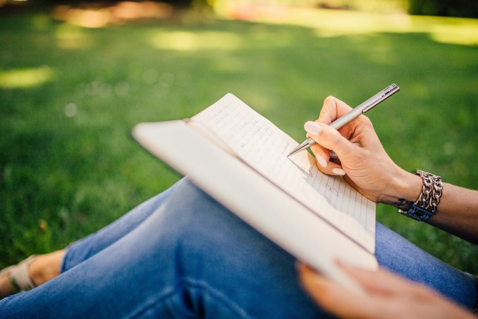 an image of a woman writting on a notepad