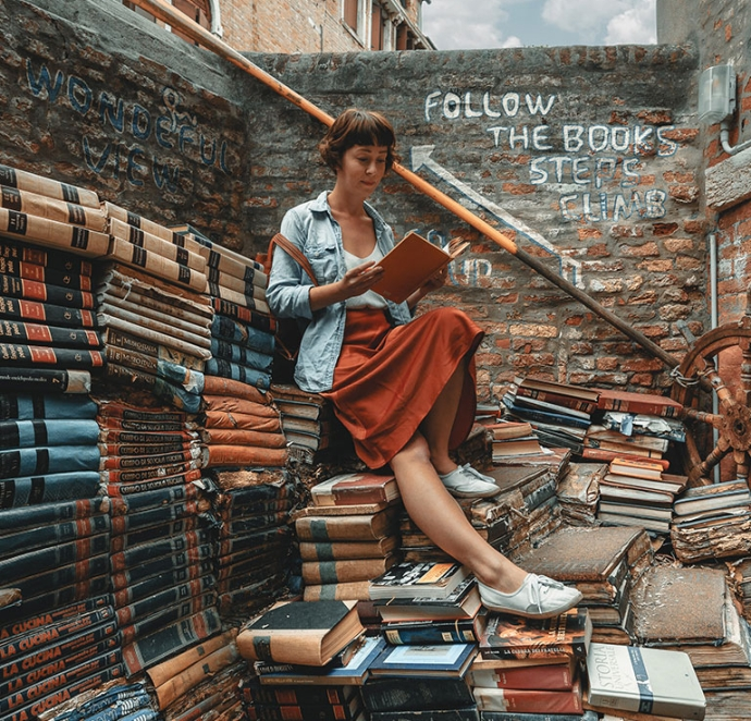 A lady sitting on top of a and surrounded by piles of book